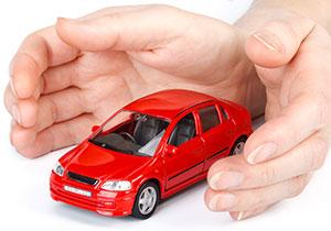 赤い車を手で包んでいる写真