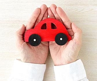 手のひらの上に赤色の車の模型を置いている写真